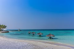 Maldives, Feb 3rd 2018 - Beach umbrellas at the shallow blue water with some divers enjoying the tropical weather of Maldives stock photo
