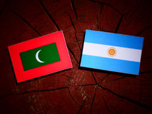 Maldives flag with Argentinian flag on a tree stump  Stock Photos