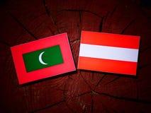 Maldives flag with Austrian flag on a tree stump  Royalty Free Stock Photo