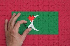 Maldives flag is depicted on a puzzle, which the man`s hand completes to fold.  stock illustration