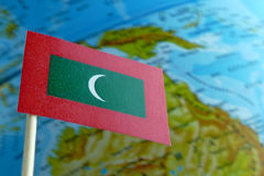 Maldives flag with a globe map as a background Stock Photo