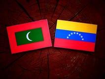 Maldives. Flag with Venezuelan flag on a tree stump isolated Royalty Free Stock Photo