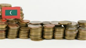 Maldives flag wavig with stack of money coins. Maldives flag waving with stack of money coins stock footage