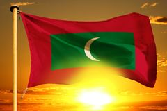Maldives flag weaving on the beautiful orange sunset with clouds background. Maldives flag weaving on the beautiful orange sunset background stock photos
