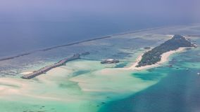 Maldives island aerial view, luxury water villas resort and wooden pier. Beautiful sky and clouds and luxury beach background stock images
