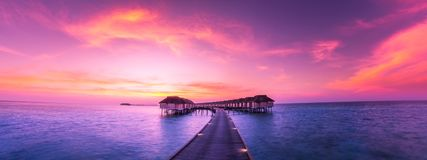 Maldives Island Panorama, Luxury Water Villas Resort And Wooden Pier. Beautiful Sky And Clouds And Luxury Beach Background Royalty Free Stock Image