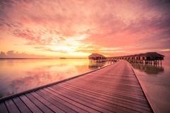 Maldives island sunset. Water bungalows resort at islands beach. Indian Ocean, Maldives. Sunset on Maldives island, luxury water villas resort and wooden pier royalty free stock photo