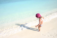Maldives islands. A girl with red hat on the beach looking into the blue water Stock Photos