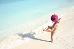 Maldives islands. A girl with red hat on the beach looking into the blue water Royalty Free Stock Image