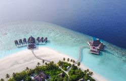 Tropical paradise resort on a sunny day. Maldives - Jul 29, 2017: Aerial view of a tropical paradise resort on the edge of a coral reef on a sunny day stock images