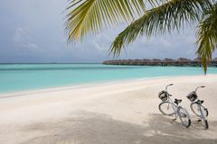 Tropical paradise resort with two bikes during a sunny day. Maldives, July 29, 2017: Tropical paradise resort on a sunny day with two bikes on the beach royalty free stock photo