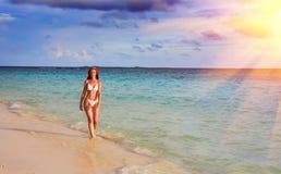 maldives La mujer delgada joven entra en un bañador en el agua poco profunda del mar fotografía de archivo