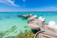 Maldives loungers and wooden pathway and sea view. Relaxing Maldives island outdoor beach scene royalty free stock photo
