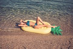 Maldives or Miami beach water. Girl sunbathing on beach with air mattress. Summer vacation and travel to ocean. Woman on Caribbean sea in Bahamas. Pineapple royalty free stock photos