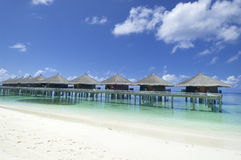 Maldives resort bungalows. Tropical resort bungalows in shallow water near sandy beach. Maldive Islands stock photography