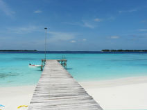 Maldives sea and sand. Jetty through sand and sea in sunny day Stock Images