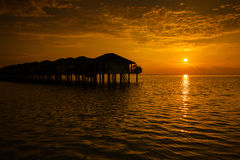 Maldives sunset with water villas silhouette Royalty Free Stock Image