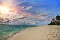 Maldives. Sunshine through clouds light the beach with palm trees.  Stock Image