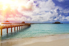 Maldives. The turquoise sea in sunshine and the wooden bridge over water Stock Photography