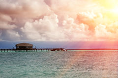 Maldives. The turquoise sea in sunshine and the wooden bridge over water Stock Photos