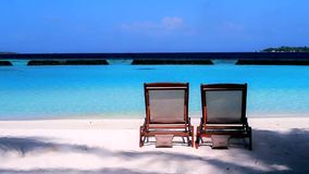Maldives. Two relaxing beach chairs in front of Indian Ocean. Maldives. Two relaxing beach chairs in front of blue silent water stock footage