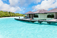 Maldives. Villa on piles on water against island Stock Photos