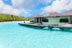 Maldives. Villa on piles on water against island Stock Photos