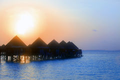 Maldives.   Villas on water in beams of sunset sun Stock Photos