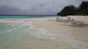 Maldives, waves on the beach, a little storm and a sand castle on the beach. Clouds on the sky stock video
