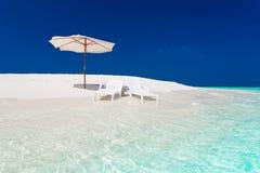 Maldives, white parasol and sunbed stock image