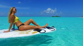P02806 Maldives white sandy beach 1 people a young beautiful woman sitting relaxing on paddle board on sunny tropical. Maldives white sandy beach 1 people a Stock Photography