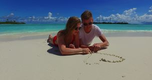 Maldives white sandy beach 2 people young couple man woman drawing love heart together with fingers on sunny