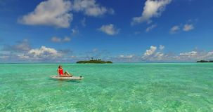 Maldives white sandy beach 2 people young couple man woman paddleboard rowing on sunny tropical paradise island. With aqua blue sky sea water ocean 4k stock footage