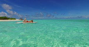 Maldives white sandy beach 2 people young couple man woman paddleboard rowing on sunny tropical paradise island. With aqua blue sky sea water ocean 4k stock video