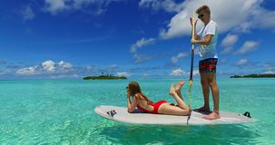Maldives white sandy beach 2 people young couple man woman paddleboard rowing on sunny tropical paradise island. With aqua blue sky sea water ocean 4k stock video footage