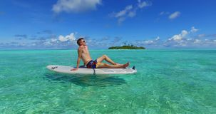 Maldives white sandy beach 1people young couple man woman paddleboard rowing on sunny tropical paradise island. Maldives white sandy beach 1 people young couple stock video