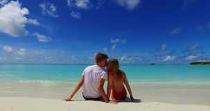 Maldives white sandy beach 2 people a young couple man woman sitting together on sunny tropical paradise island. With aqua blue sky sea water ocean 4k stock footage