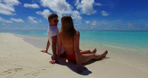 Maldives white sandy beach 2 people a young couple man woman sitting together on sunny tropical paradise island. With aqua blue sky sea water ocean 4k stock video