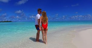Maldives white sandy beach 2 people a young couple man woman walking together in love on sunny tropical paradise