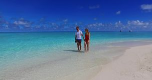 Maldives white sandy beach 2 people a young couple man woman walking together in love on sunny tropical paradise. Island with aqua blue sky sea water ocean 4k stock video