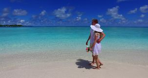 Maldives white sandy beach 2 people a young couple man woman walking together in love on sunny tropical paradise. Island with aqua blue sky sea water ocean 4k stock footage
