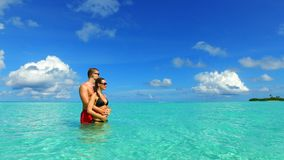 P02953 Maldives white sandy beach 2 people a young couple man woman romantic love on sunny tropical paradise island with Royalty Free Stock Images