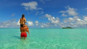 P02951 Maldives white sandy beach 2 people a young couple man woman romantic love on sunny tropical paradise island with Stock Image