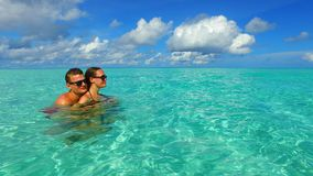 P02928 Maldives white sandy beach 2 people a young couple man woman romantic love on sunny tropical paradise island with Stock Image