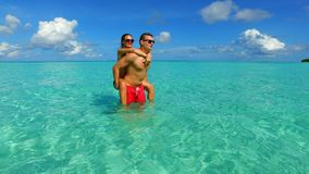P02931 Maldives white sandy beach 2 people a young couple man woman romantic love on sunny tropical paradise island with Stock Photography