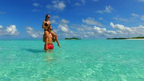 P02940 Maldives white sandy beach 2 people a young couple man woman romantic love on sunny tropical paradise island with Royalty Free Stock Photos