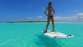 P02828 Maldives white sandy beach 1 people a young woman standing on paddle board on sunny tropical paradise island with Royalty Free Stock Photography