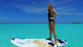 P02826 Maldives white sandy beach 1 people a young woman standing on paddle board on sunny tropical paradise island with Stock Images