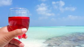 P01473 Maldives white sandy beach red drink cocktail on sunny tropical paradise island with aqua blue sky sea ocean 4k Royalty Free Stock Photo