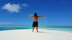 P01717 Maldives white sandy beach young man standing on sunny tropical paradise island with aqua blue sky sea ocean 4k. Maldives white sandy beach young man Stock Image